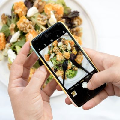 person using iPhone taking picture of food