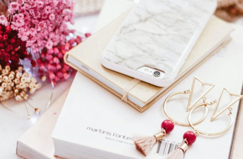 iPhone on book beside gold-colored earrings
