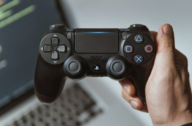 person holding black sony ps 4 game controller